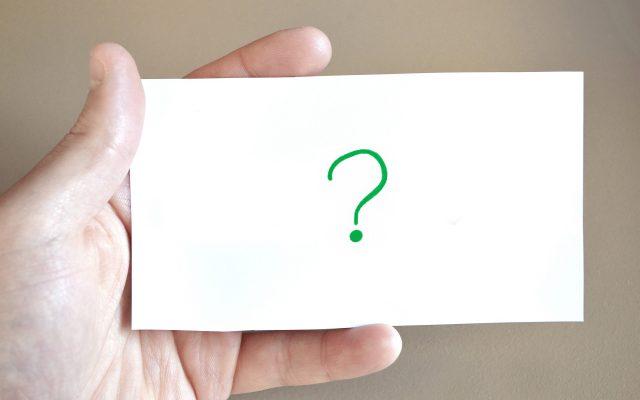 Hand die einen Zettel hält auf dem ein Fragezeichen steht